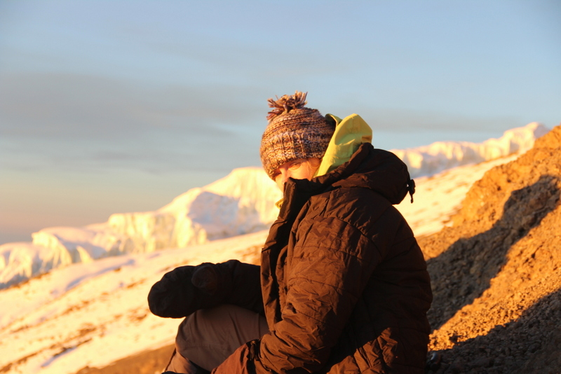 Claire, after reaching the crater rim, being recharged by the sunrise before the final push to the summit.