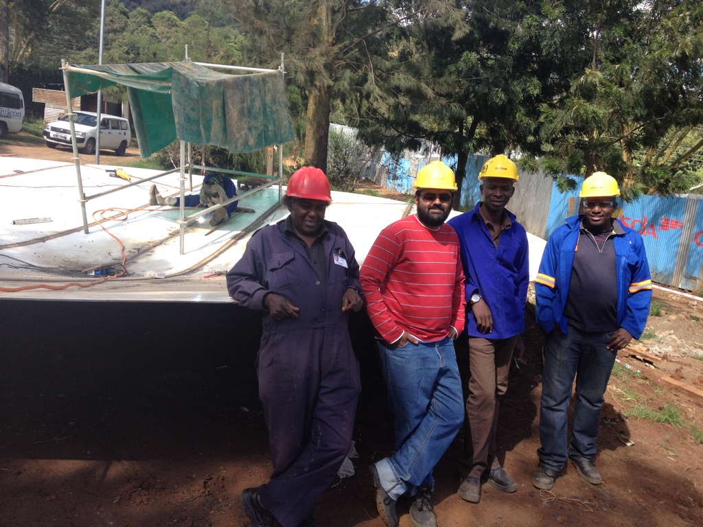 From left, Kijabe Hospital's head plumber, Civicon's Project Engineer, QA Manager, and Foreman--leaning against the recently-welded tank roof.