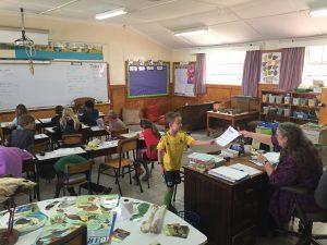 Liam hands in classwork to his 3rd grade teacher, Mrs. Hollman