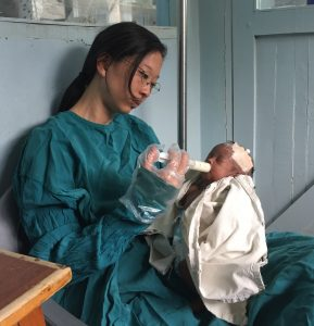 OB Catherine feeds an orphaned baby in nursery.